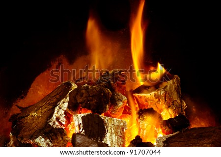 A burning log fire with glowing embers - stock photo