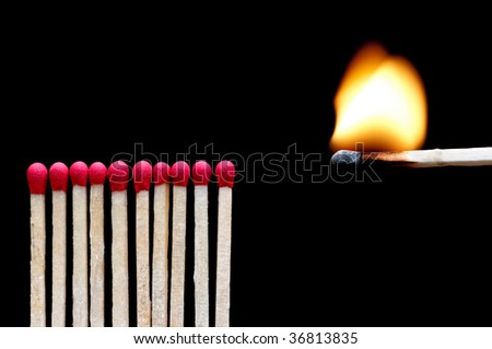 A burning match near other matches on black - stock photo