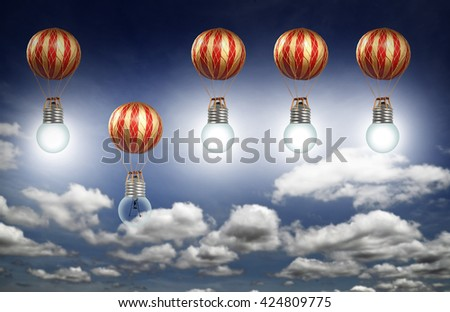 A burnout lightbulb on a colorful balloon sinking down against the other lit balloon on a blue cloudy sky for the concept of losing out due to disadvantage. - stock photo