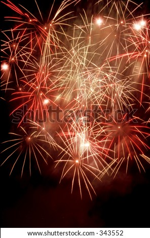 A burst of red, white and yellow fireworks in the night sky - stock photo
