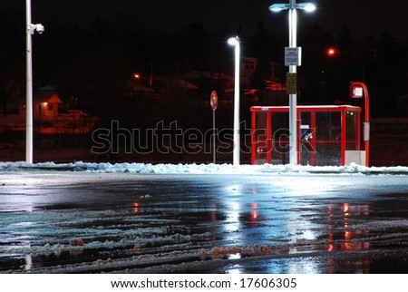 A bus stop on a cold winter night sits empty.  Lights reflect off the wet parking lot pavement. - stock photo