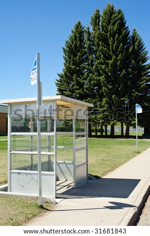 A bus stop shelter with tall trees in background