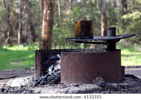 A bush campfire, with a billy boiling on the hot plate.