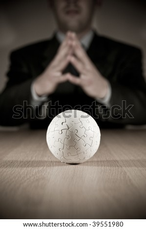 A businesman pondering with focus on a puzzle globe. - stock photo