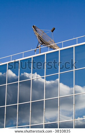 A business building topped with a satellite dish.  Glass windows reflect sky clouds.