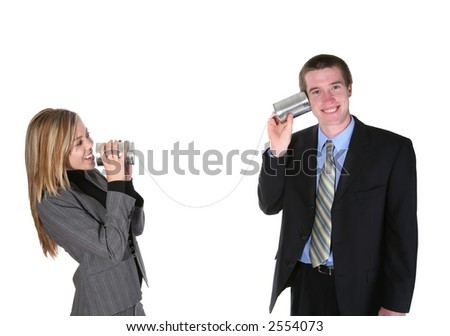 A business couple communicating on an old tin can phone - stock photo
