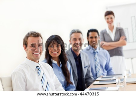 A business group showing ethnic diversity at a presentation in the office - stock photo