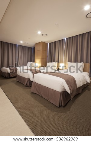 A business hotel room with triple bed, curtain, table, chair, blanket, window in seoul, korea.