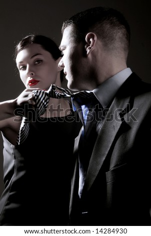 a business lady is pulling man's tie on the black - stock photo