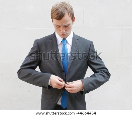 A business man adjusting his suit - stock photo