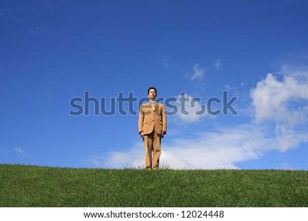 A business man alone on a meadow waiting for an order