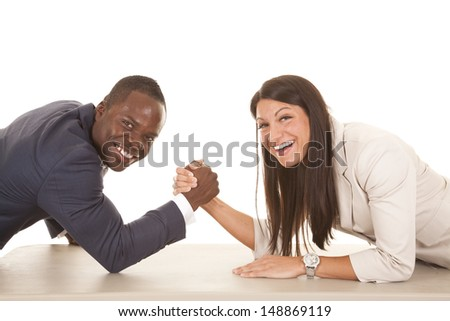 A business man and woman arm wrestling with smiles on their faces. - stock photo
