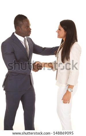 A business man and woman shake hands with a smile. - stock photo