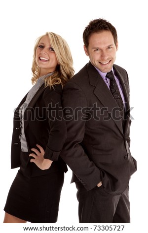 A business man and woman standing back to back with smiles on their faces.