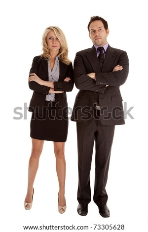A business man and woman standing side by side with their arms folded with serious expressions on their faces. - stock photo