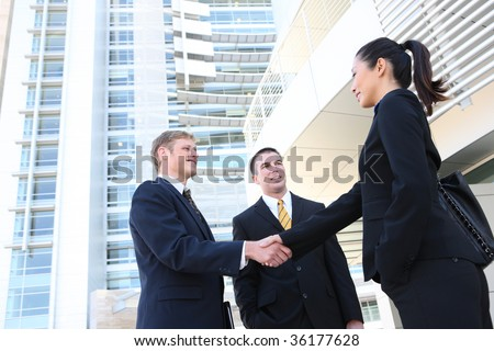 A business man and woman team at office shaking hands - stock photo