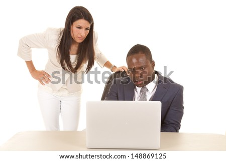 A business man and woman with serious expressions looking at the laptop.