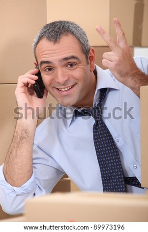 a business man calling someone in a room full of cardboard boxes - stock photo