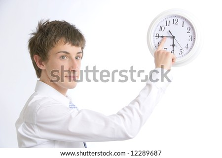 A business man changing the time on the office clock so he can go home early - stock photo