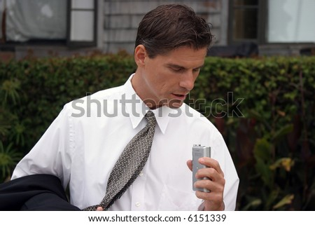 a business man dictates into his miniature tape recorder - stock photo