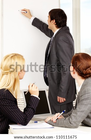 A business man drawing a plan on a whiteboard for his colleagues - stock photo