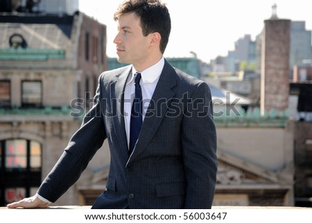 A business man dressed in a suit on a rooftop with the New York City cityscape in the background. - stock photo