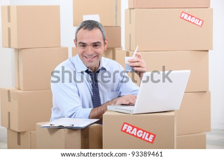 a business man drinking doing computer among cardboard boxes - stock photo