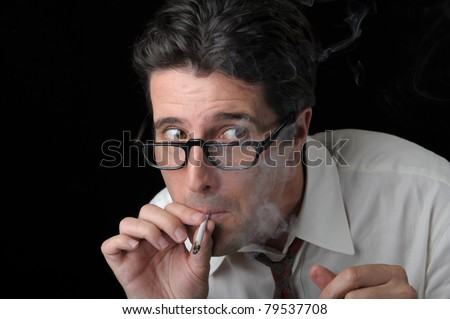 A business man furtively sneaks a hit of marijuana before heading back into the office. - stock photo