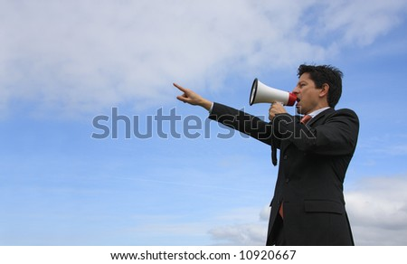 A business man giving an order with a megaphone with a blue sky as Background - stock photo