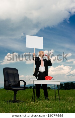 A business man holding a blank picket sign and a bullhorn in an outdoor office. - stock photo