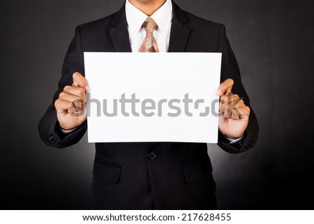 A business man holding a paper in front of his face - stock photo