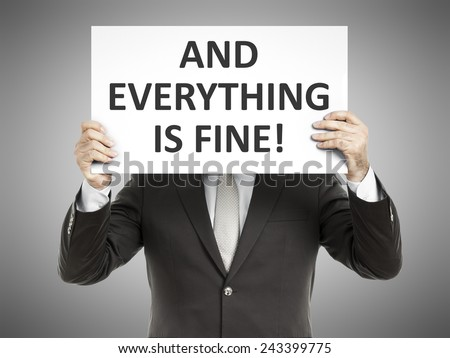 A business man holding a paper in front of his face with the message and everything is fine! - stock photo