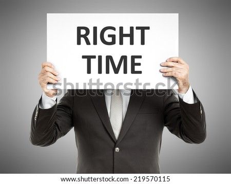 A business man holding a paper in front of his face with the text right time - stock photo