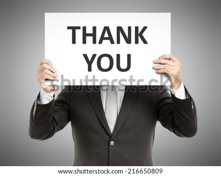 A business man holding a paper in front of his face with the text thank you - stock photo