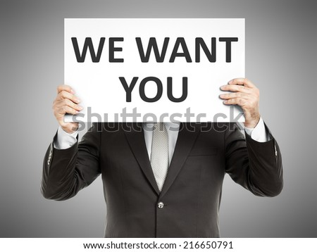 A business man holding a paper in front of his face with the text we want you - stock photo