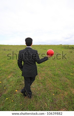 A business man holding a red ball on his hand