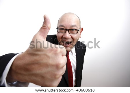 A business man holding his thumb up and smiling.