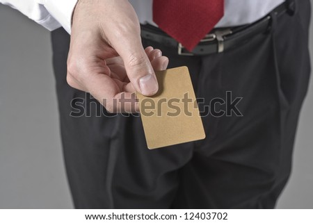 A business man holding out a blank gold credit card - stock photo