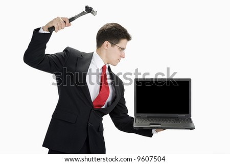 A business man in a black suit wearing a white shirt and red tie getting ready to hit a black laptop with a hammer. - stock photo