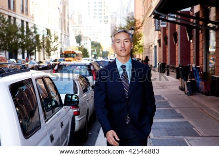A business man in a city setting on a sidewalk - stock photo
