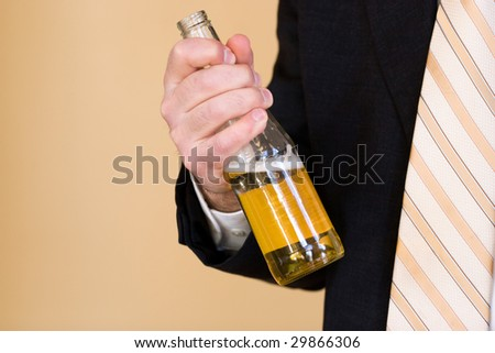 A business man in a suit holding a beer. Benjamin Franklin said that Beer is living proof that God loves us and wants us to be happy. - stock photo
