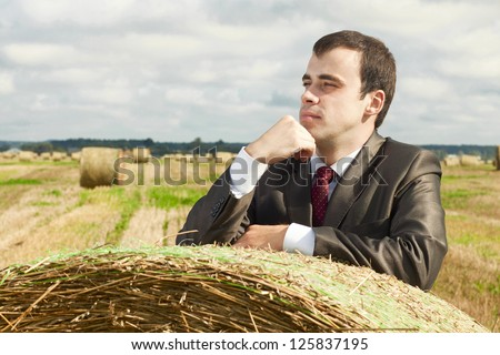 A business man in a suit is based on the stack of hay