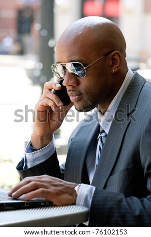 A business man in his early 30s talking on his cell phone and working on his laptop or netbook computer. - stock photo