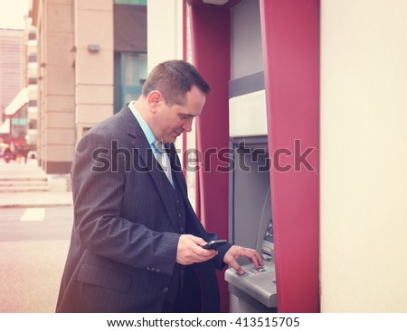 A business man is holding a phone and withdrawing money from his account at an automatic teller machine downtown for a finance or banking concept. - stock photo
