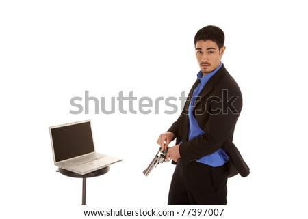 A business man is loading is gun and standing by his computer. - stock photo