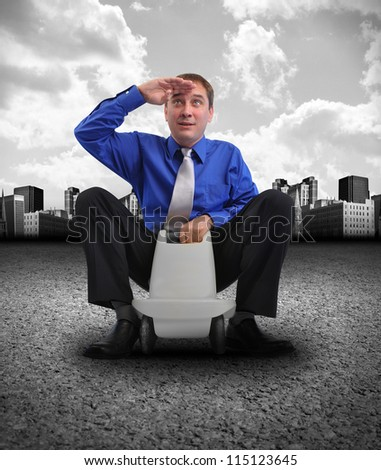 A business man is looking forward and sitting on a toy car on a road with a city and clouds in the background. use it for a vision or energy concept. - stock photo