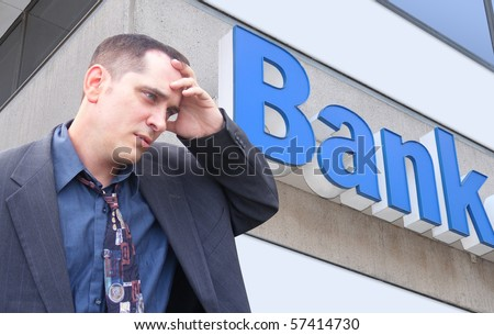 A business man is standing in front of a bank and looks stressed and worried. Can represent finance, the economy, or an investment theme. - stock photo