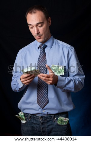 A business man is surprised and very happy because is has just earned a lot of money. His pocket are full of wads. Conceptual image for business success, rich people, income, ... - stock photo