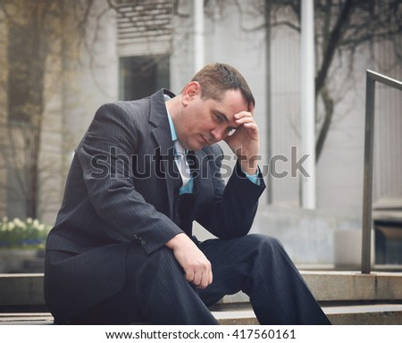 A business man is worried and stressed in a suit outside a city for a financial, unemployment or economy concept. - stock photo