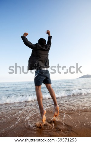 A business man jumping on the beach, freedom, success concept - stock photo